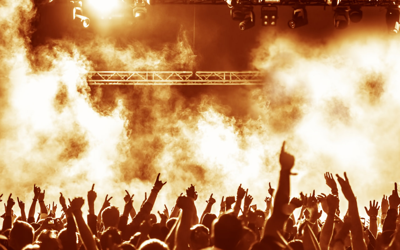 Crowd cheering at a gig, stage obscured by smoke