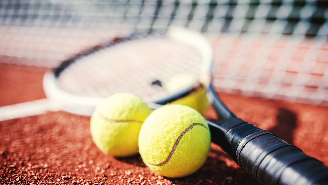 Tennis balls and racquet in front of net